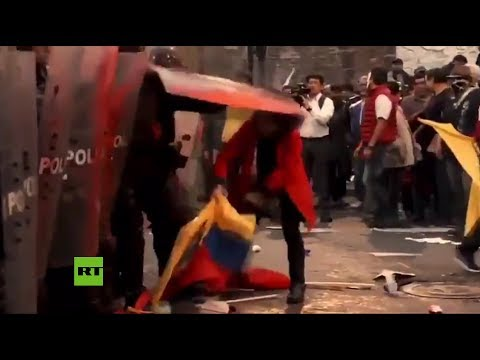 policía-patea-a-una-mujer-por-recoger-la-bandera-de-ecuador-del-suelo