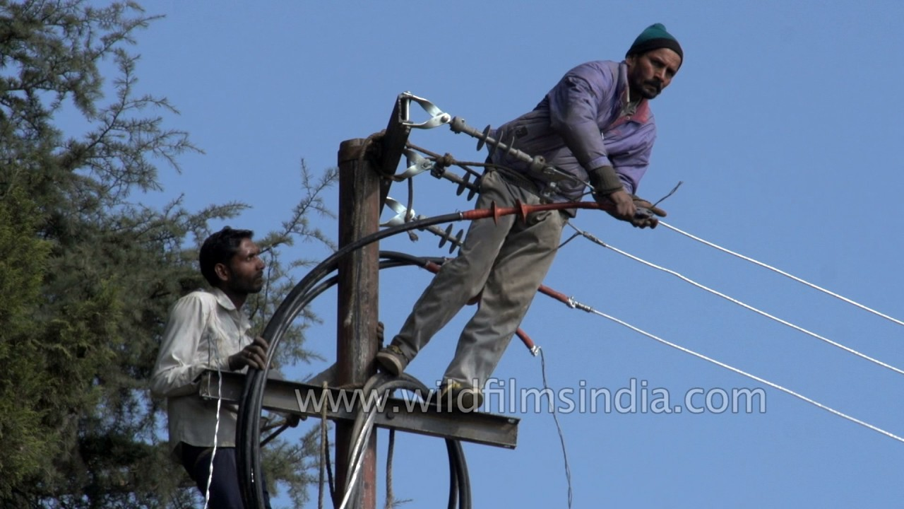 Dangerous work standing atop electricity poles and