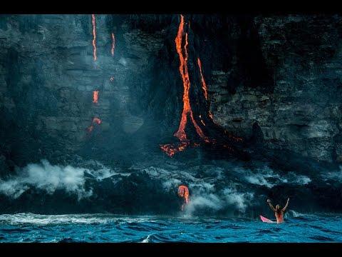 Surfista Alison Teal llegando al extremo para surcar las olas, cuando se acerca a la lava del volcán Kilauea en Hawái