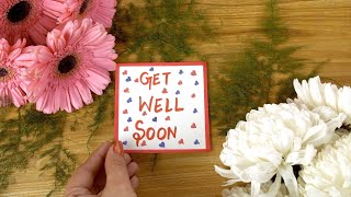 Woman hands placing get well soon wishing card on a decorated wooden table