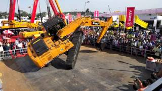 Extreme stunts performed by excavator at an auto show