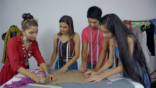 Young successful designer teaching pattern placement to her students - College life
