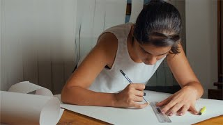 An architecture student working on a drawing project at home