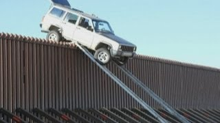 Mexican smugglers leave Jeep teetering on edge of California border fence