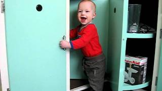 Funny Baby Boy Playing In Revolving Corner Cupboard