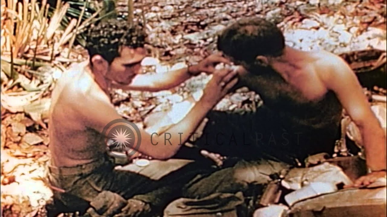 United States soldier bandages other soldier's wound at a field in Saipan,  Pacifi   HD Stock Footage