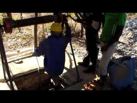 Entering a small scale mine shaft for antimony ore stibnite with a winch hoist in Zimbabwe
