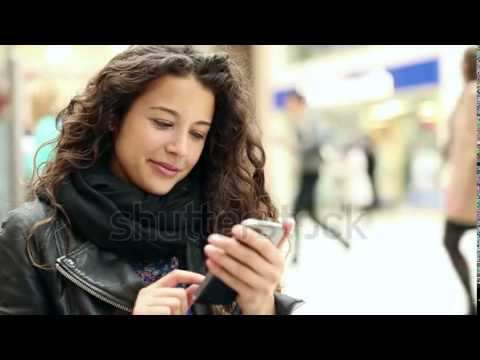 stock footage attractive young woman using her touch screen mobile cell phone and smiling to herself