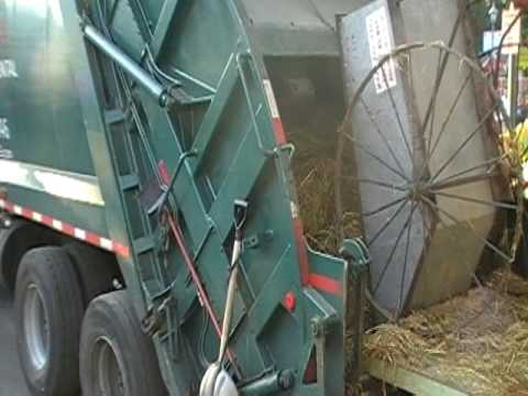 Dumping straw in rear loader garbage truck from sheep barn Minnesota State Fair