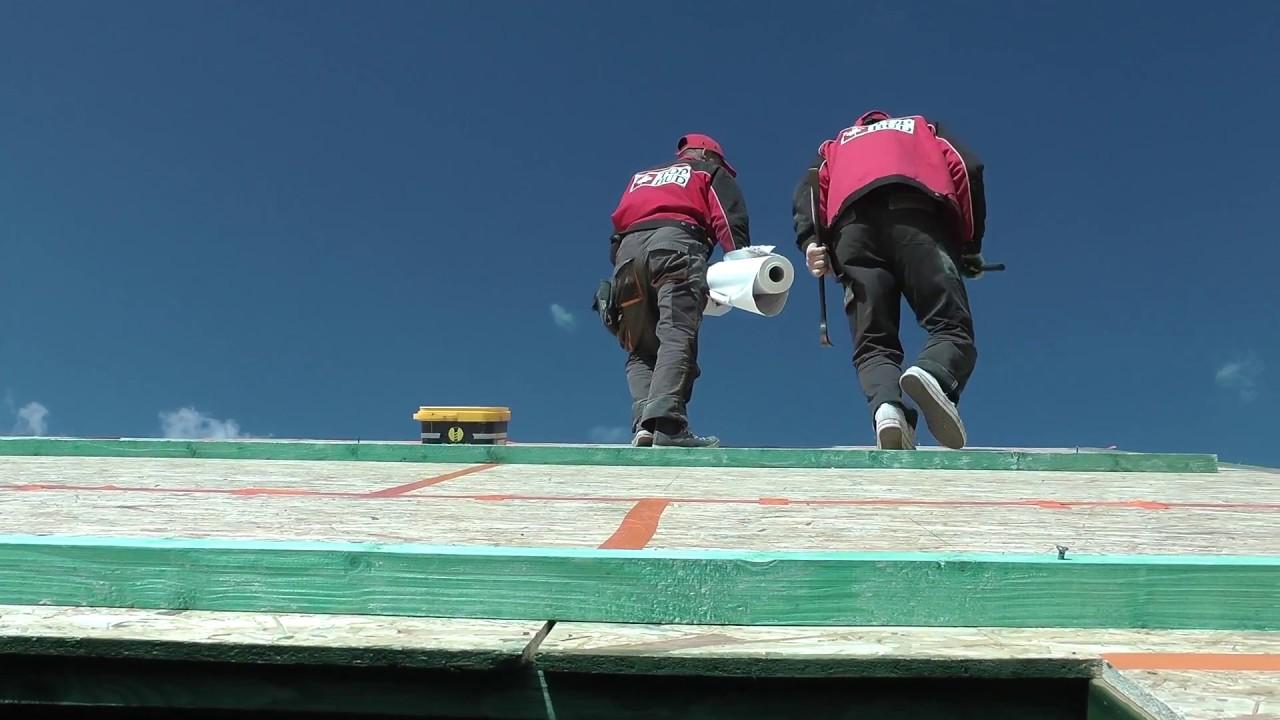 Układanie warstwy wiatroizolacji na ścianie i dachu domu ...