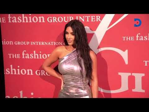 Kanye West embraces Kim Kardashian as they pose for photos at the Fashion Group International Stars Gala\'s eve