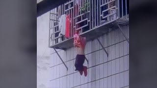 Footage: Two men save girl hanging by neck from fourth-story window