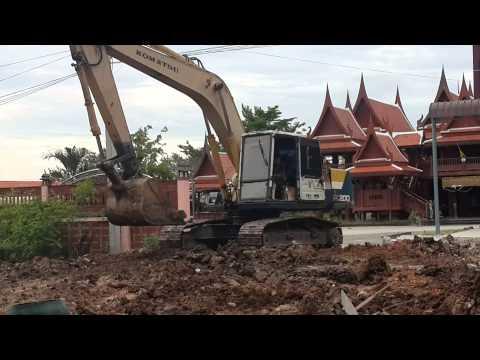รถตักดินทำงานหน้าบ้านทรงไทยอยุธยา