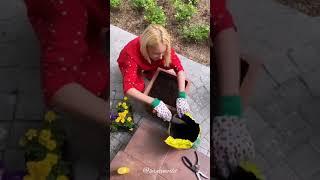 Лера Кудрявцева высаживает цветы в большие горшки около дома