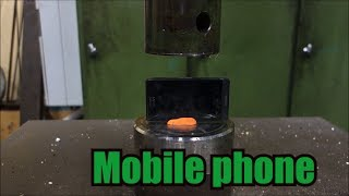 Crushing mobile phone with hydraulic press