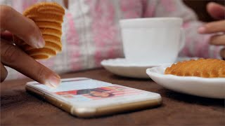 Shot of an Indian women scrolling news her phone while having tea and biscuits