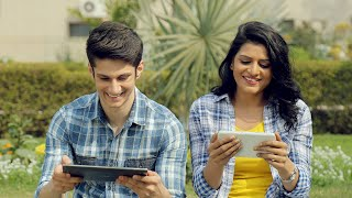 Mid shot of young happy couple sitting outside in a park and playing games on tablet
