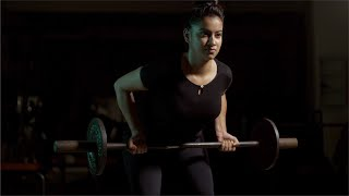 Pretty Indian fit girl / female doing dead lift exercise with barbell weights in the gym