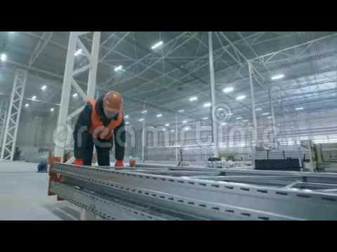 Man carries metal construction in new modern industry ware house