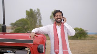 Indian farmer happily talking over a phone call - agricultural field in background