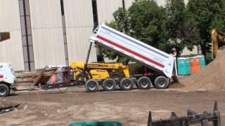 Double Dump Truck back end dumping in a huge pile of soil