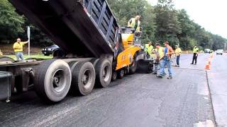 Dump truck feeding asphalt into the paver as the paver pushes the truck