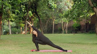 A young girl practicing parsvakonasana / extended side angle yoga pose outside in a park