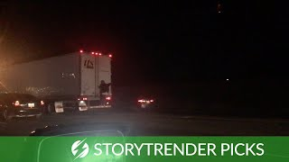 Hitchhiker Clings To Back Of A Lorry On Interstate