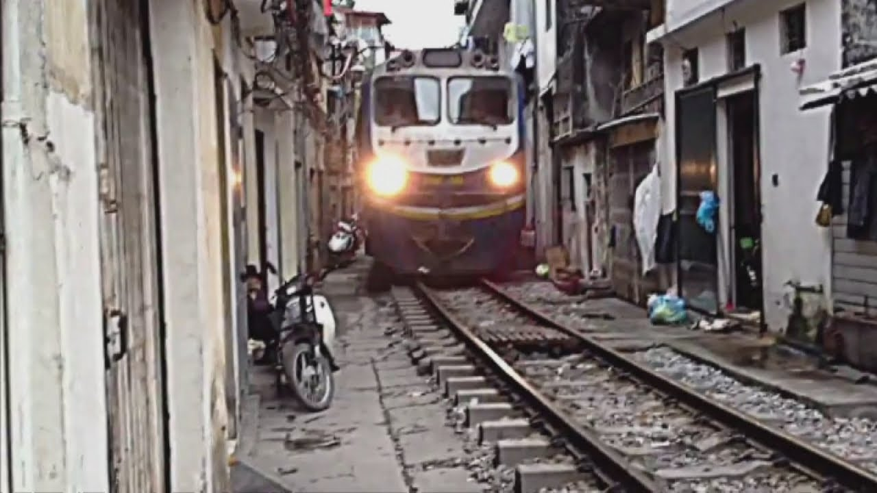 Train travels through narrow gap inbetween houses in for House of tracks