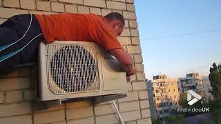 Viral Video UK: Man holds onto air conditioner while repairing it