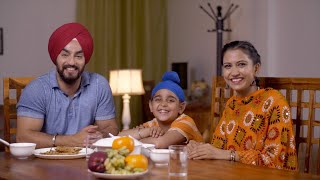 Happy Sikh Punjabi family having lunch together in a dining room -  family concept