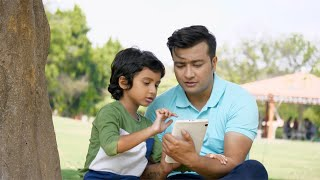 Indian father teaching new things to his son on a tablet - the concept of digital education