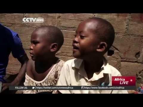 Ugandan youth sheltering orphaned children