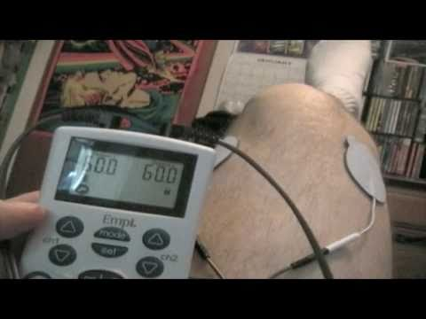 tens-device-demonstration.-electric-stim-unit-on-knees.-chronic-pain-treatment.