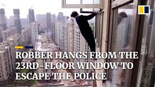 robber-hangs-from-the-23rd-floor-window-to-escape-the-police-in-china