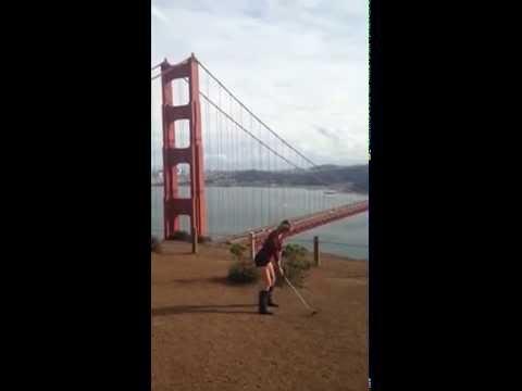 Girl hits golf ball at Golden Gate Bridge, San Francisco CA
