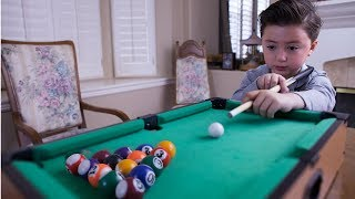 6 Year-old billiard prodigy playing with a mini pool table