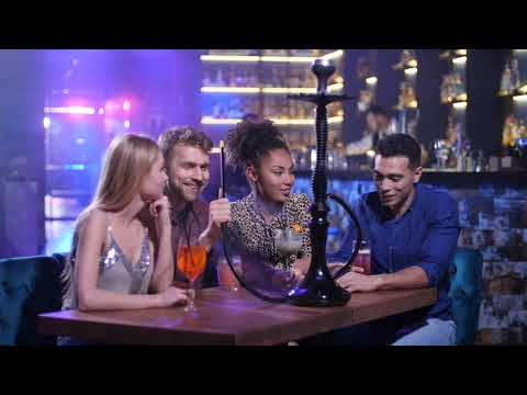 Happy Friends Talking Smoking Hookah In Nightclub YTG5J2C