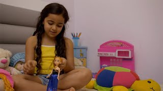 Active little child girl playing with doll in her room - children play concept