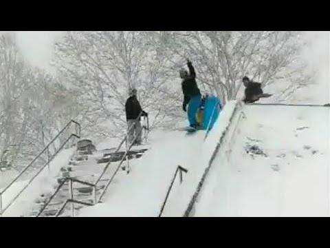 Grown men snowboard in downtown streets of Boston during nor'aster