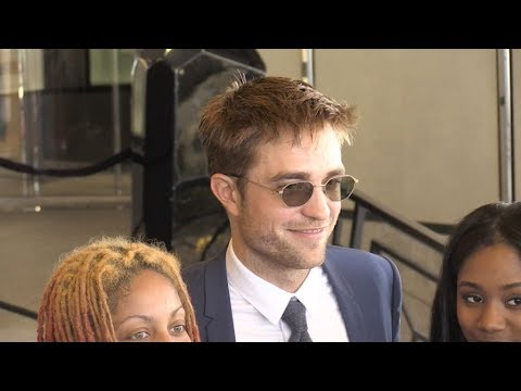 Robert Pattinson poses with member of the cast at hotel in Cannes