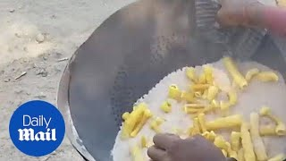 A man cooks raw potato snacks using hot sand - Daily Mail