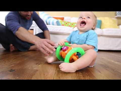 Smyths Toys -Bright Starts Lights Baby Roll & Glow Monkey