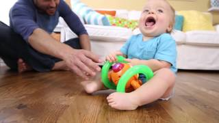 Smyths Toys -Bright Starts Lights Baby Roll & Glow Monkey