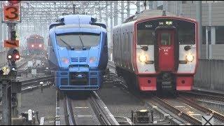 雨の大分駅を出発する日豊本線上り特急883系青いソニックと下り815系