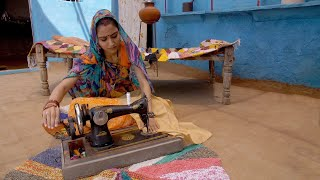 Indian village lady stitching her clothes on a sewing machine - rural concept