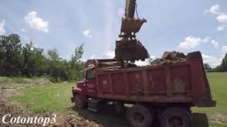 John Deere excavator loading a Ford L8000 dump truck