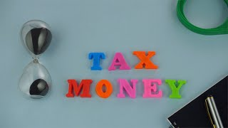 "Tilt shot of colorful words ""Tax Money"" placed together on the blue background"