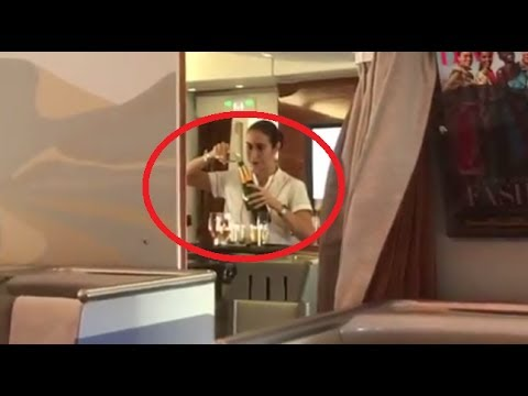 Emirates Airlines stewardess pour unused champagne back into bottles