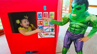 सुपरहीरो बच्चे अली और एड्रियाना वेंडिंग मशीन किड्स टॉय के साथ खेलते हैं